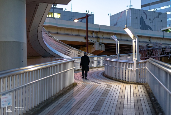 Man walking during evening time on one of the many pedestrian overpasses available in Yokohama
