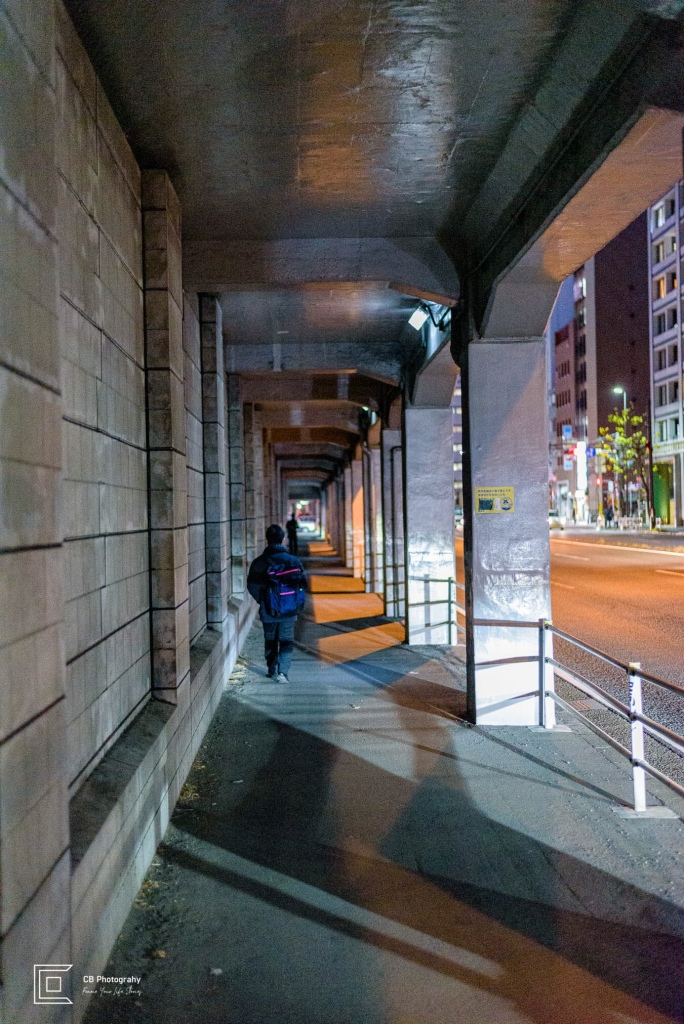 Night view of man walking under an underpass near be a street