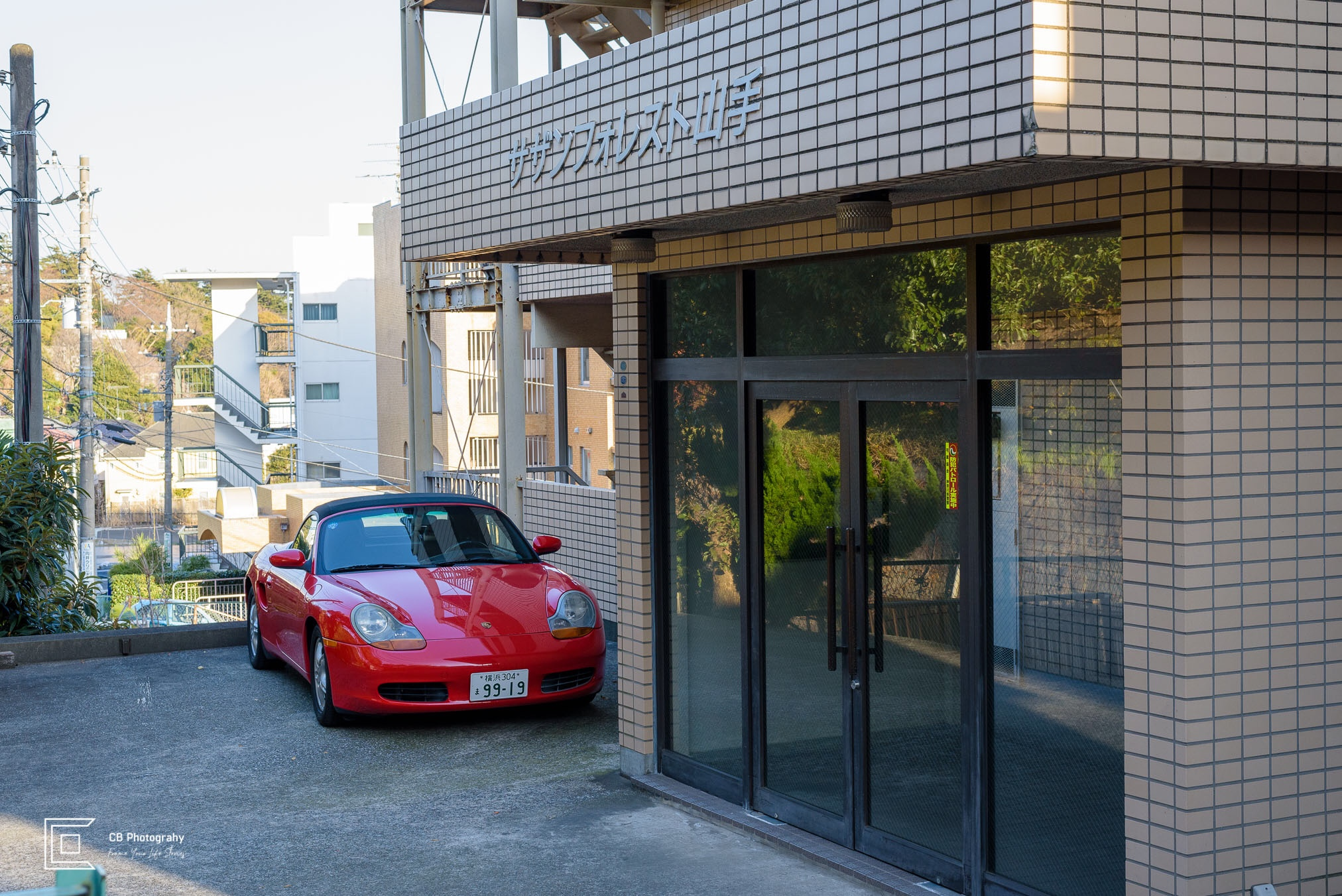 Red Porsche convertible parked in front of a building